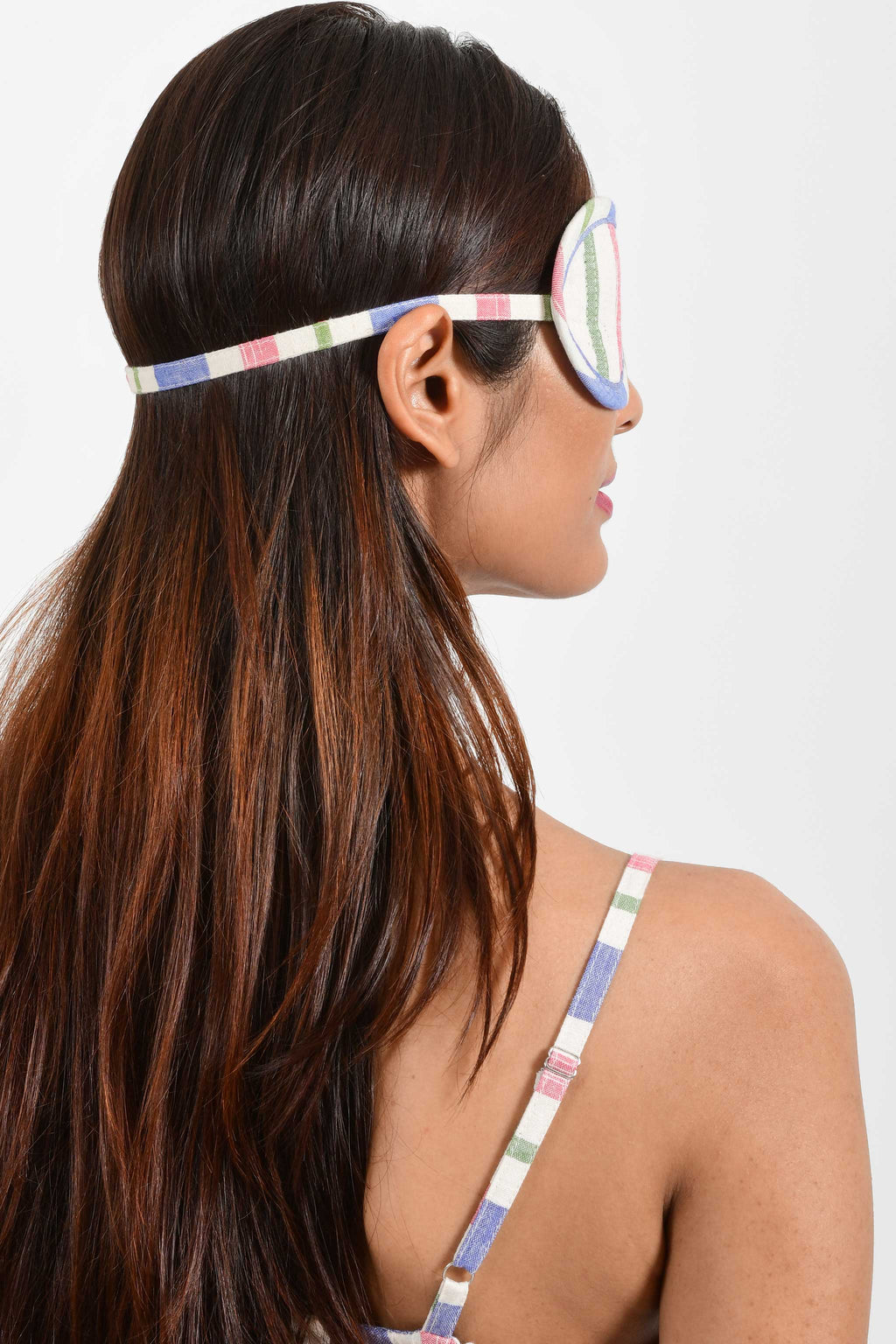 Back portrait of an Indian female womenswear fashion model wearing a multi-coloured striped handspun and handwoven khadi cotton eye mask by Cotton Rack.
