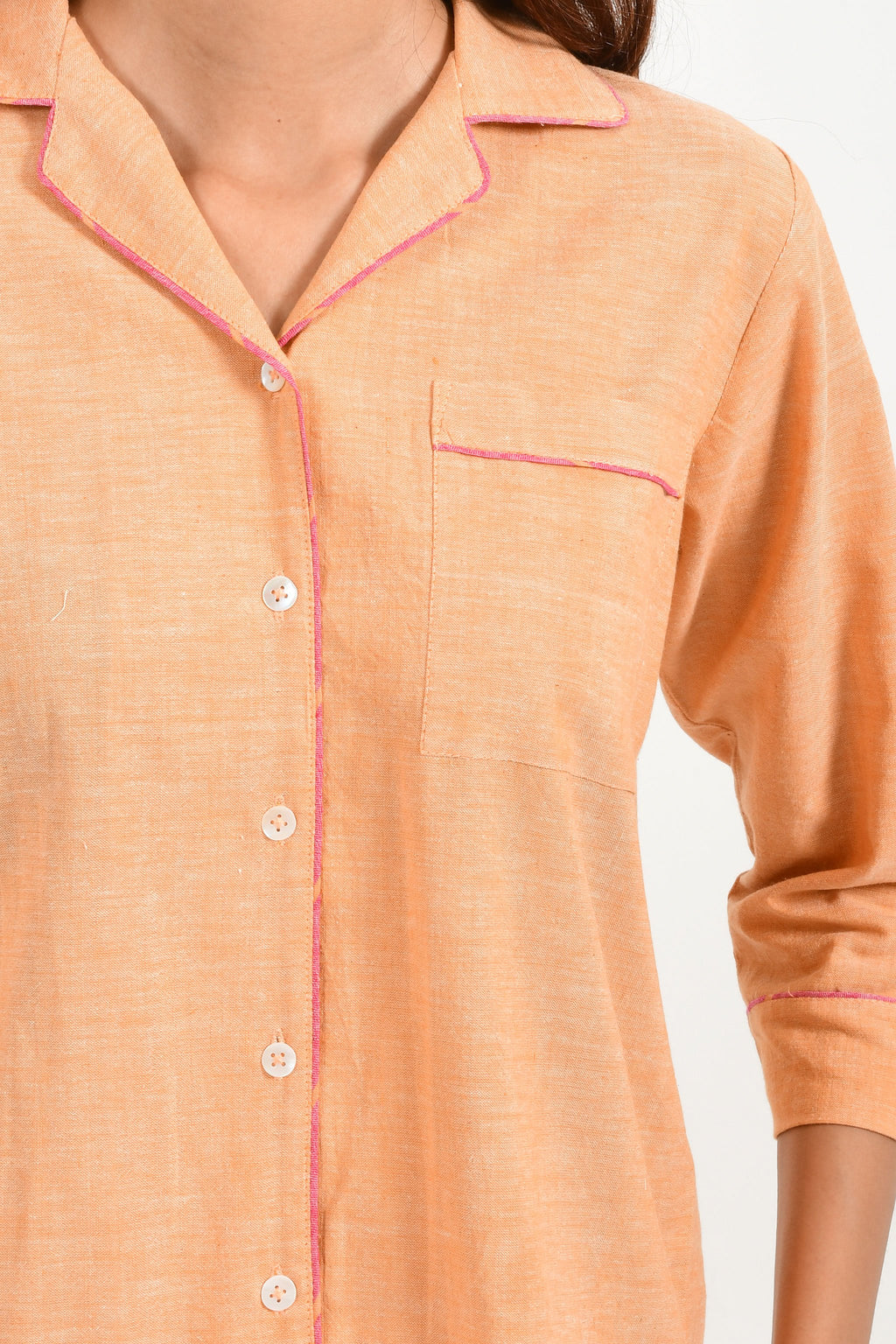 Close-Up of an Indian female womenswear fashion model in azo-free dyed handspun and handwoven khadi cotton nightwear pyjama & shirt in orange chambray by Cotton Rack.