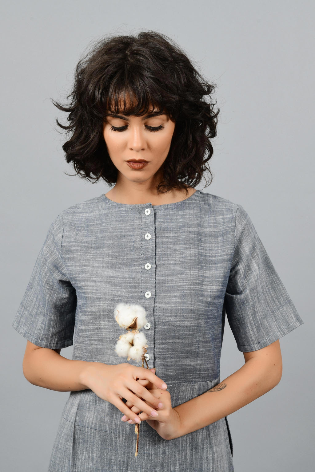 A female womenwear model in blue khadi dress looking down at the cotton bolls that she's holding in her hands.