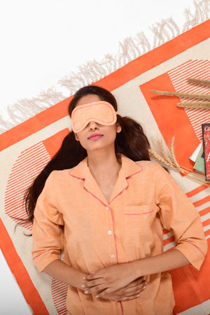 An Indian female womenswear fashion model wearing a orange chambray handspun and handwoven khadi cotton eye mask by Cotton Rack and lying on an orange carpet.
