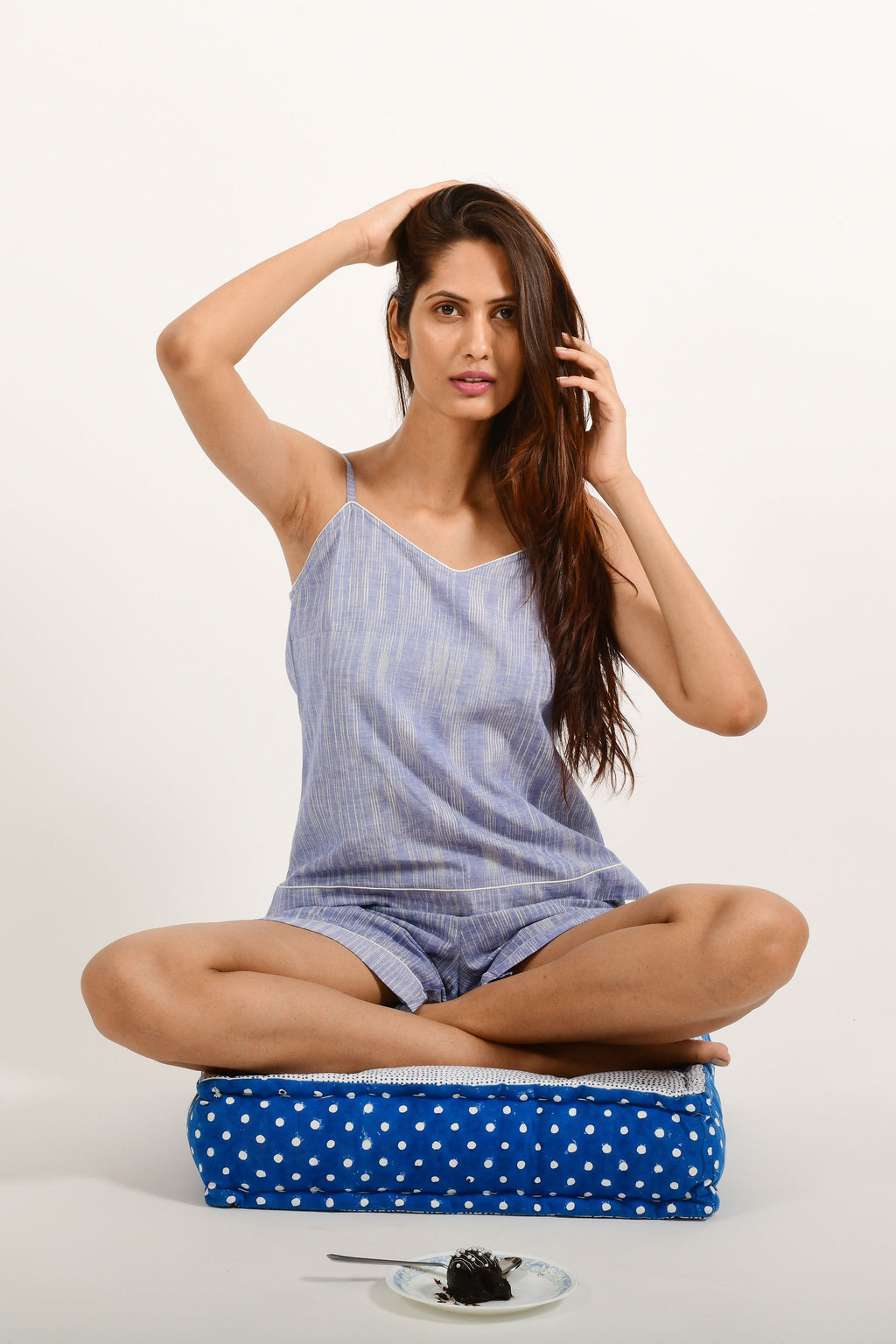 Stylized pose of an Indian female womenswear fashion model in azo-free space dyed blue handspun and handwoven khadi cotton spaghetti top and boxers by Cotton Rack.