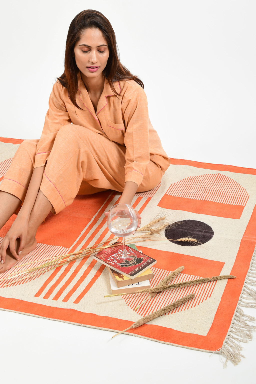 Creative pose of an Indian female womenswear fashion model in azo-free dyed handspun and handwoven khadi cotton nightwear pyjama & shirt in orange chambray by Cotton Rack and sitting on a handmade carpet with books and wine glass filled with water.