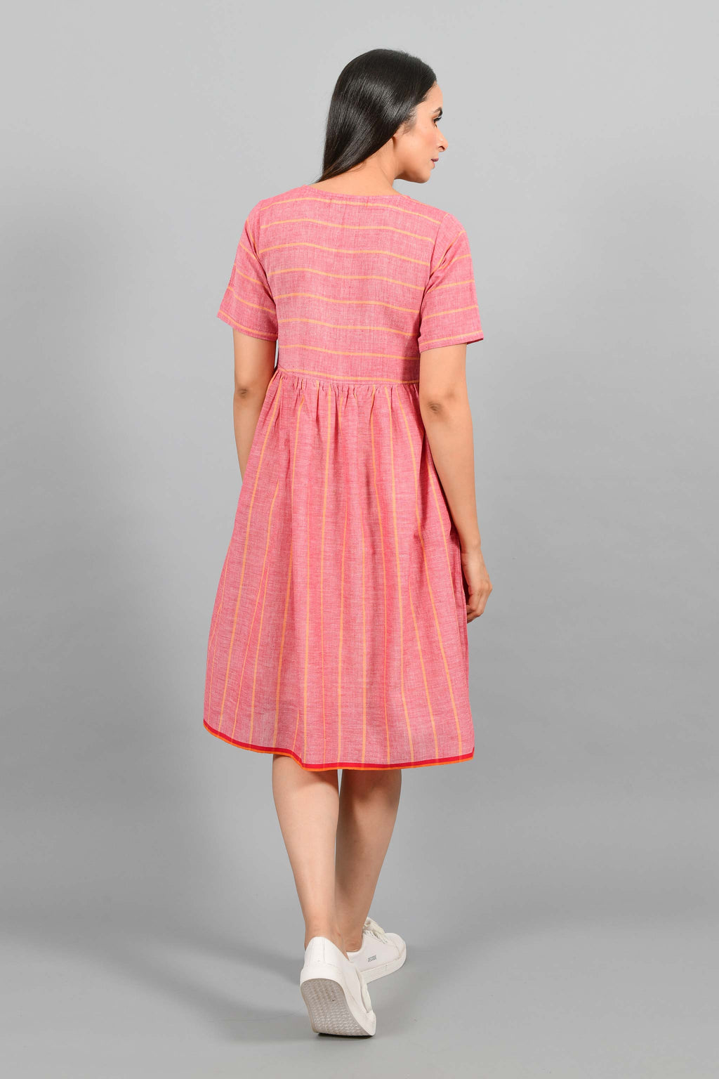 Back pose of an Indian female womenswear fashion model in a red chambray handspun and handwoven khadi cotton with orange stripes by Cotton Rack. The dress has front buttoned yoke and gathers at waist.