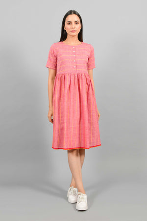 Front pose of an Indian female womenswear fashion model in a red chambray handspun and handwoven khadi cotton with orange stripes by Cotton Rack. The dress has front buttoned yoke and gathers at waist.