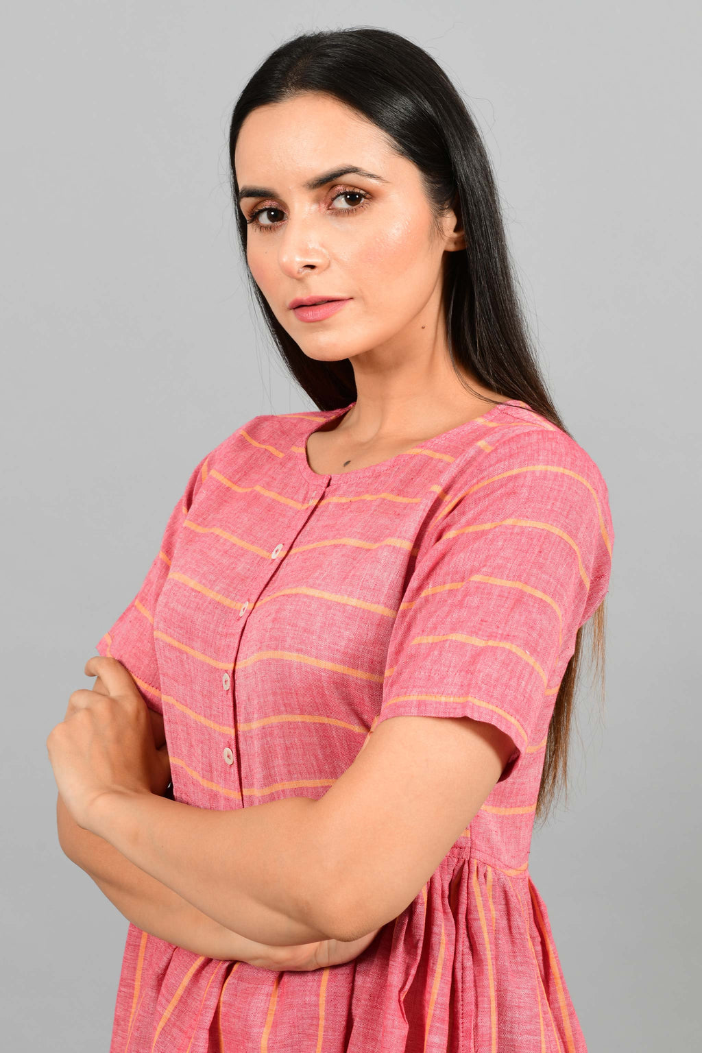 Portrait pose of an Indian female womenswear fashion model in a red chambray handspun and handwoven khadi cotton with orange stripes by Cotton Rack. The dress has front buttoned yoke and gathers at waist.