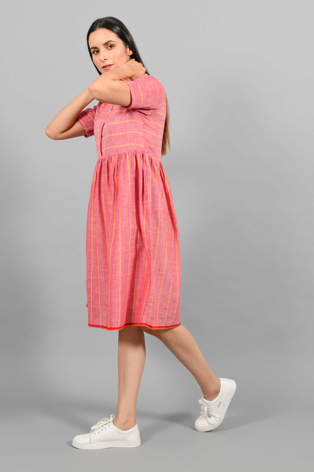 Side walking pose of an Indian female womenswear fashion model in a red chambray handspun and handwoven khadi cotton with orange stripes by Cotton Rack. The dress has front buttoned yoke and gathers at waist.