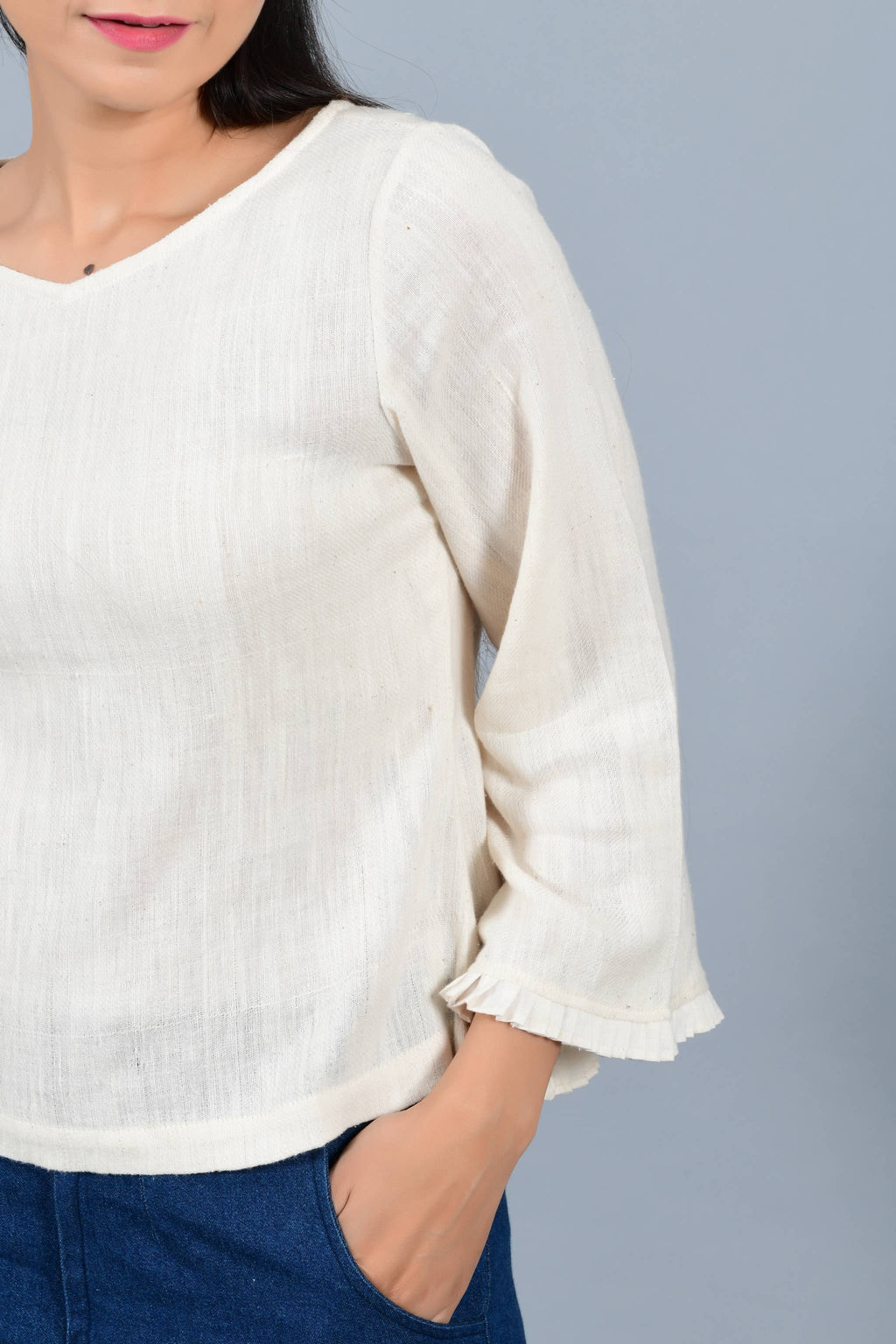 Front Close-up of an Indian female womenswear fashion model in an off-white Cashmere Cotton Top with bell sleeves made using handspun and handwoven khadi cotton by Cotton Rack.