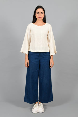 Front pose of an Indian female womenswear fashion model in an off-white Cashmere Cotton Top with bell sleeves made using handspun and handwoven khadi cotton by Cotton Rack.