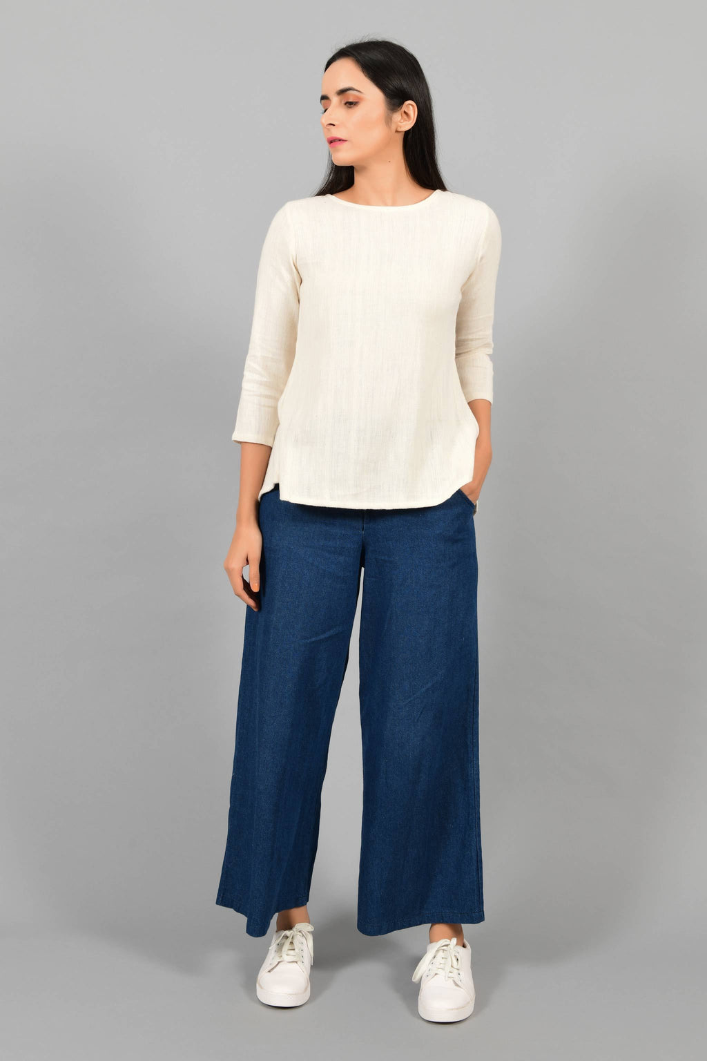 Front pose of an Indian female womenswear fashion model in an off-white Cashmere Cotton Top with box pleated back and quarter sleeves made using handspun and handwoven khadi cotton by Cotton Rack.