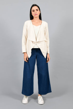 Front pose of an Indian female womenswear fashion model in a short off-white Cashmere Cotton jacket-shrug with extra wide lapels, made using handspun and handwoven khadi cotton by Cotton Rack.