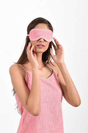 Front portrait of an Indian female womenswear fashion model wearing a pink chambray handspun and handwoven khadi cotton eye mask by Cotton Rack.