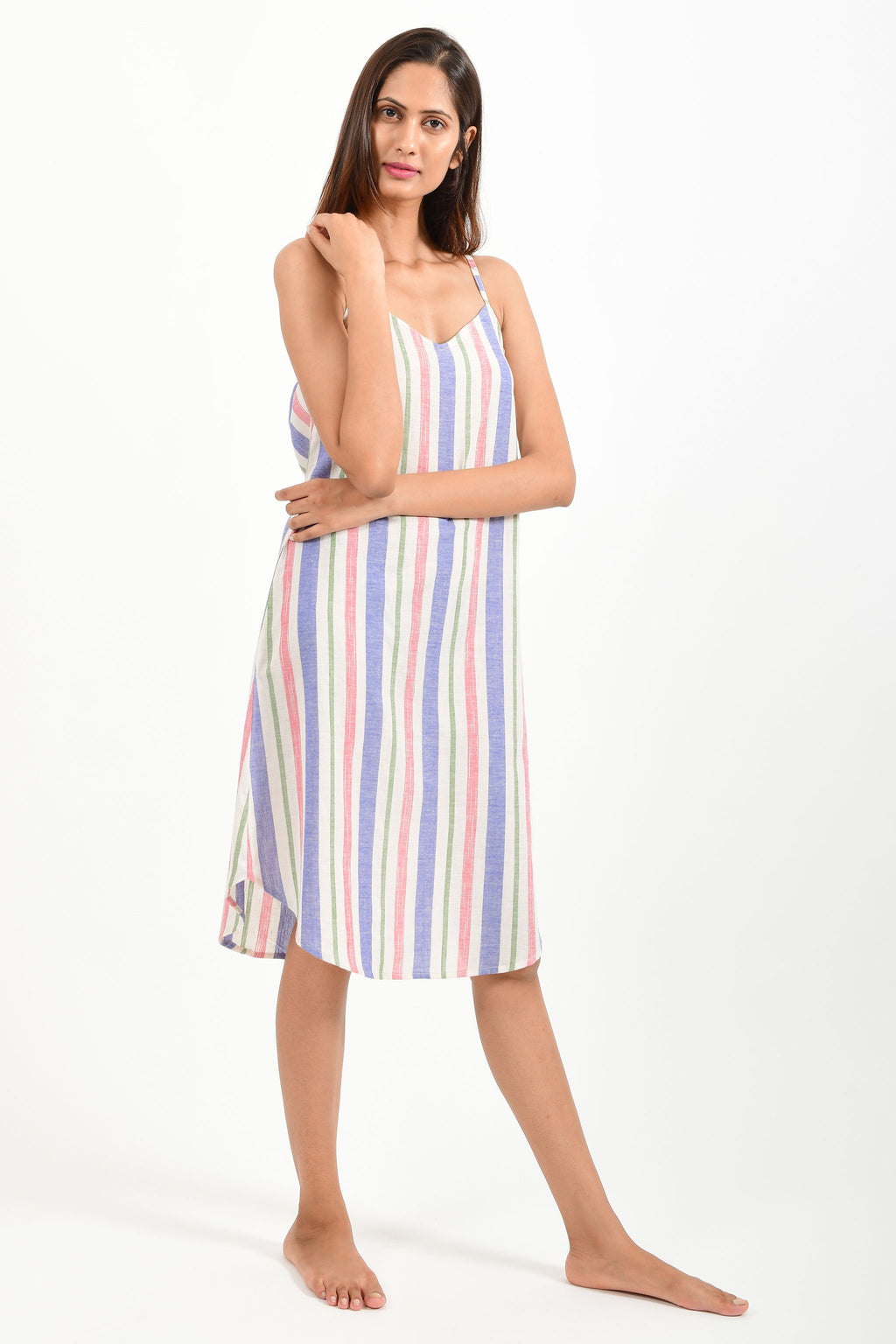 Front pose of an Indian female womenswear fashion model in an mutli colored striped handspun and handwoven khadi cotton spaghetti dress by Cotton Rack.