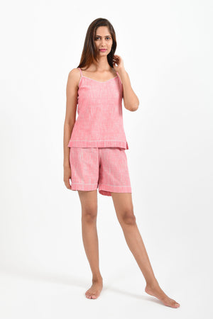 Front pose of an Indian female womenswear fashion model in azo-free space dyed pink handspun and handwoven khadi cotton spaghetti top and boxers by Cotton Rack.