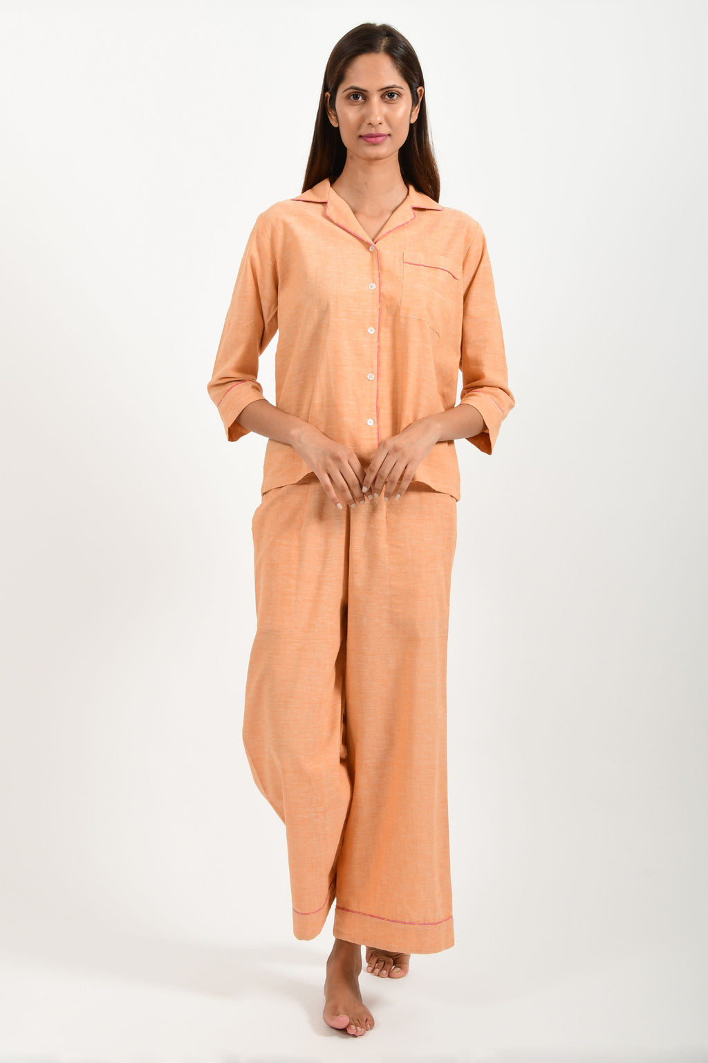 Front pose of an Indian female womenswear fashion model in azo-free dyed handspun and handwoven khadi cotton nightwear pyjama & shirt in orange chambray by Cotton Rack.
