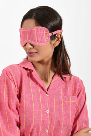 Front portrait of an Indian female womenswear fashion model wearing a red with orange stripe chambray handspun and handwoven khadi cotton eye mask by Cotton Rack.