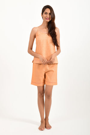 Front pose of an Indian female womenswear fashion model in azo-free dyed orange chambray handspun and handwoven khadi cotton spaghetti top and boxers by Cotton Rack.