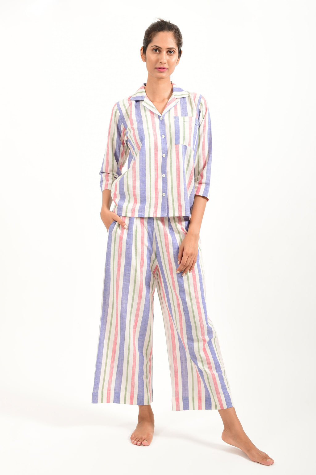 Front pose of an Indian female womenswear fashion model in a candy colored striped azo-free dyed handspun and handwoven khadi cotton nightwear pyjama & shirt by Cotton Rack.