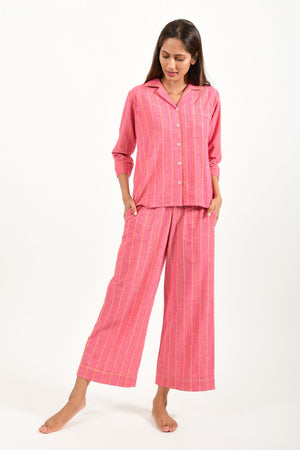 Front pose of an Indian female womenswear fashion model in azo-free dyed handspun and handwoven khadi cotton nightwear pyjama & shirt with red base and orange stripes by Cotton Rack.