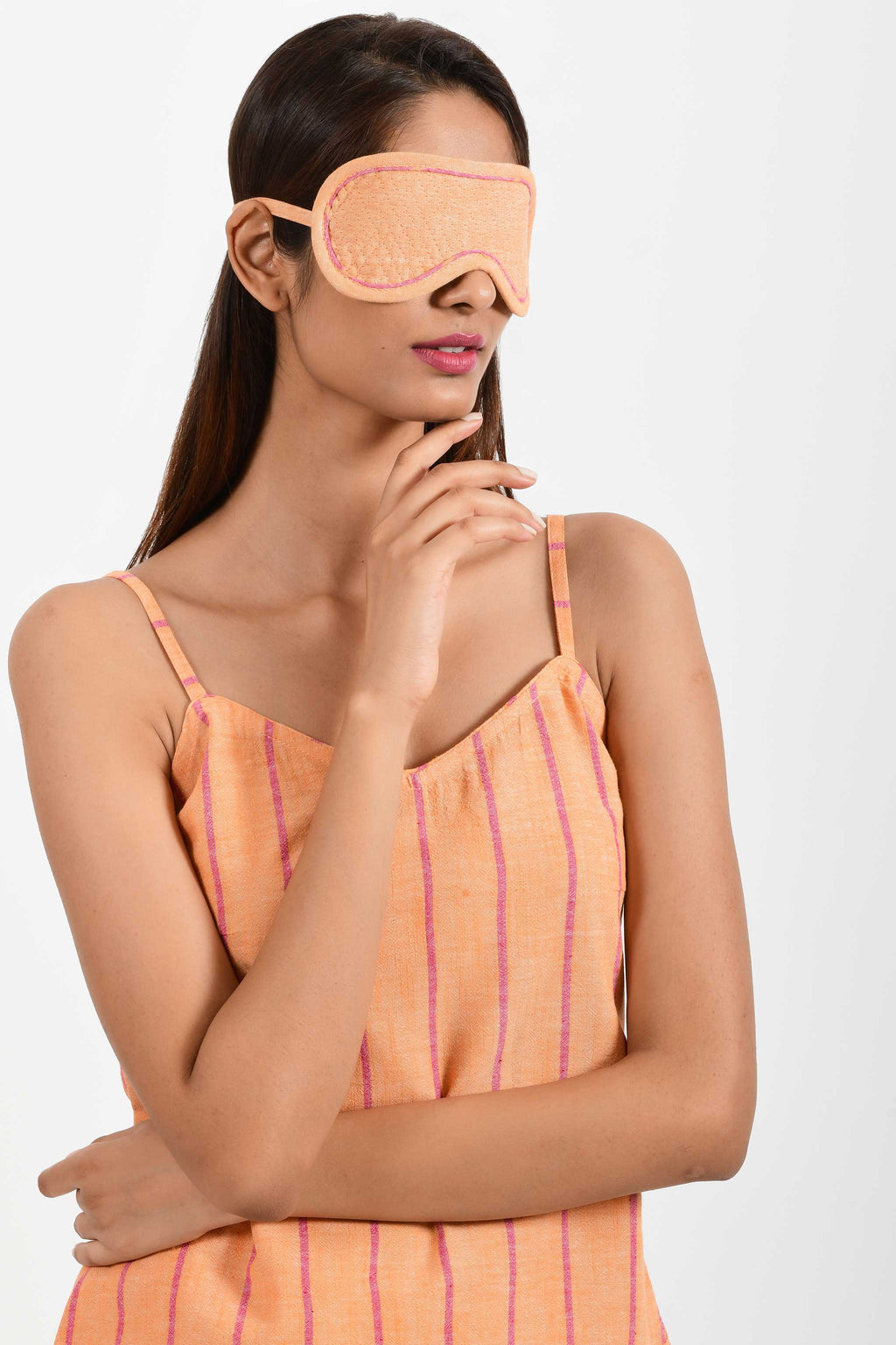 Front portrait of an Indian female womenswear fashion model wearing a orange chambray handspun and handwoven khadi cotton eye mask by Cotton Rack.