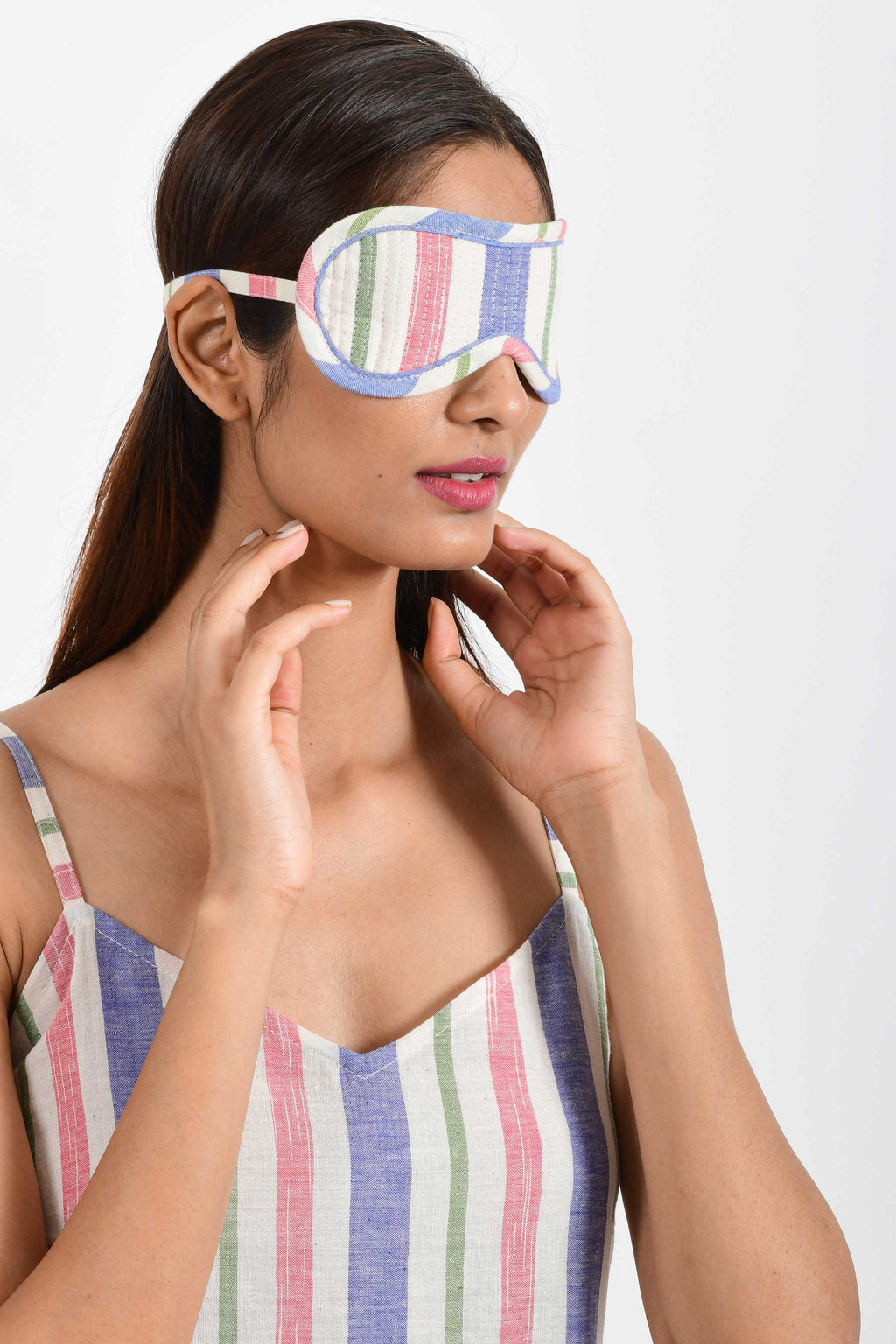 Front portrait of an Indian female womenswear fashion model wearing a multi-coloured striped handspun and handwoven khadi cotton eye mask by Cotton Rack.