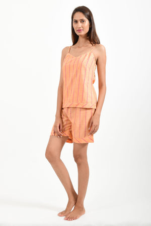 Front pose of an Indian female womenswear fashion model in azo-free dyed orange chambray (with red stripes) handspun and handwoven khadi cotton spaghetti top and boxers by Cotton Rack.