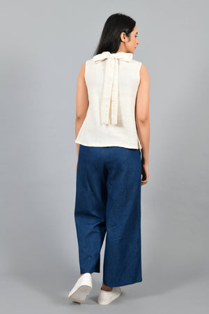 Back pose of an Indian female womenswear fashion model in an off-white Cashmere Cotton Top with a bow collar made with handspun and handwoven khadi cotton by Cotton Rack.