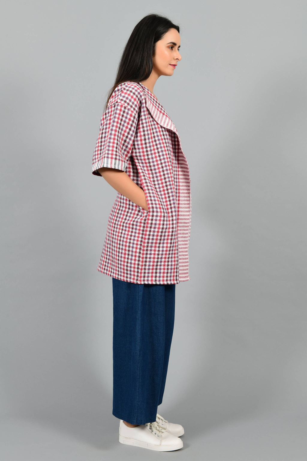 Side pose of an Indian Womenswear female model wearing Red and Blue handspun and handwoven khadi long Jacket over an off-white cashmere cotton dress by Cotton Rack.