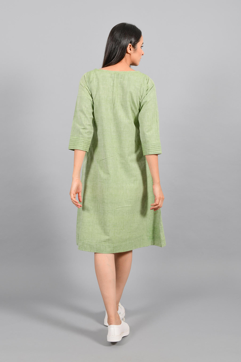 Back pose of an Indian female womenswear fashion model in a olive green chambray handspun and handwoven khadi cotton dress-kurta with pintucks on front by Cotton Rack.