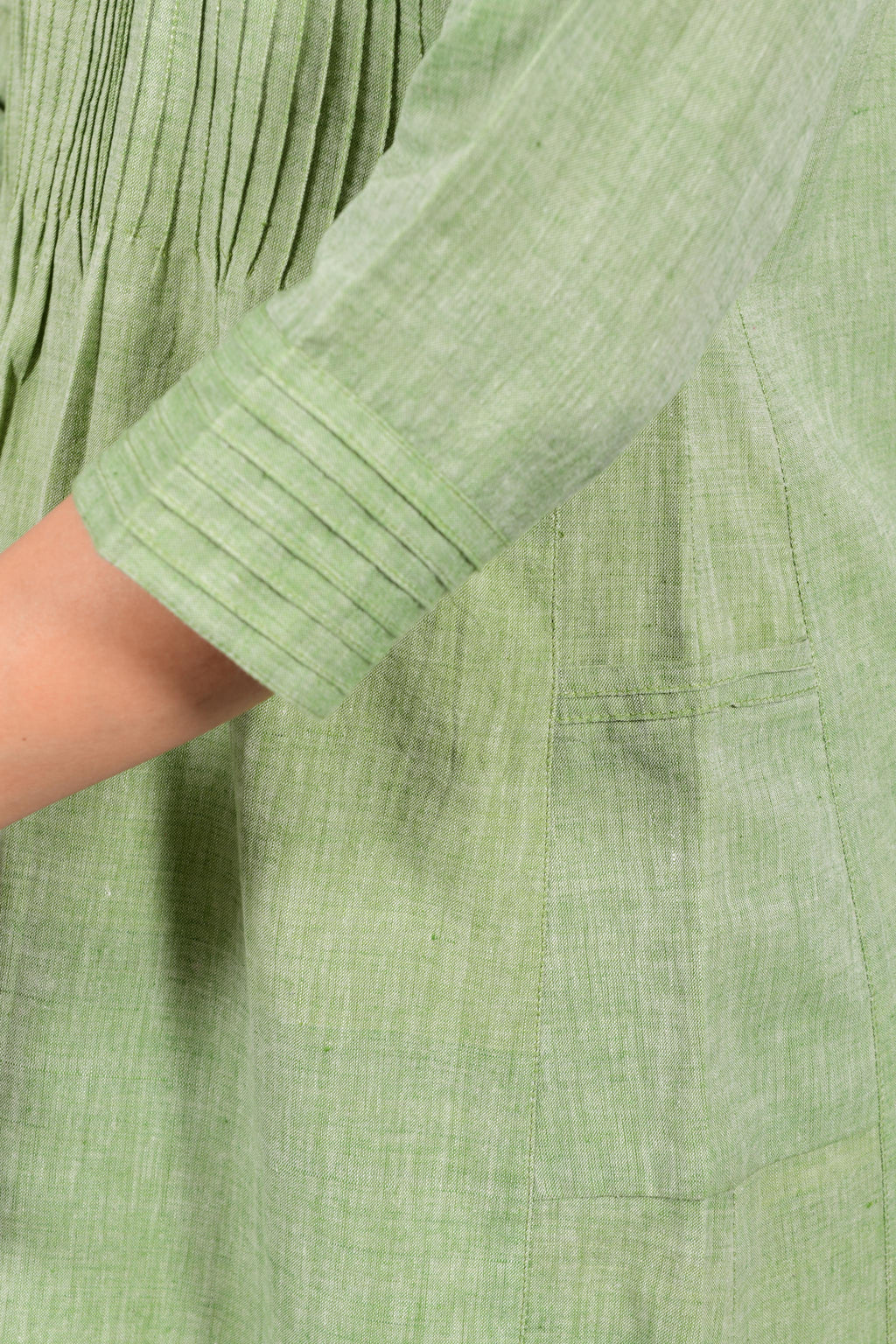 Close up details of a olive green chambray handspun and handwoven khadi cotton dress-kurta with pintucks on front by Cotton Rack.