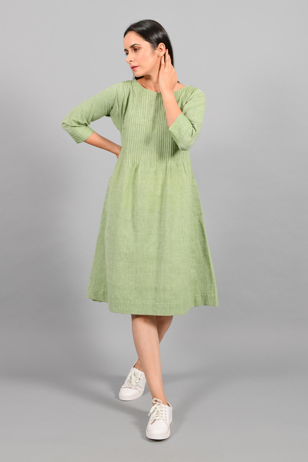 Front stylised pose of an Indian female womenswear fashion model in a olive green chambray handspun and handwoven khadi cotton dress-kurta with pintucks on front by Cotton Rack.