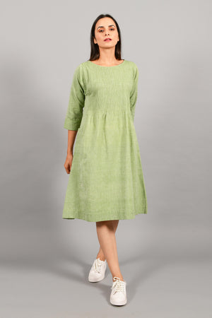 Front pose of an Indian female womenswear fashion model in a olive green chambray handspun and handwoven khadi cotton dress-kurta with pintucks on front by Cotton Rack.