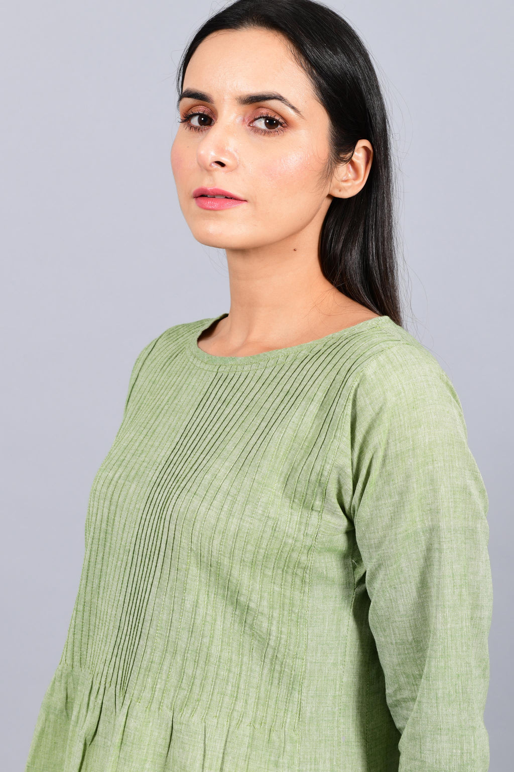 Close up portrait of an Indian female womenswear fashion model in a olive green chambray handspun and handwoven khadi cotton dress-kurta with pintucks on front by Cotton Rack.