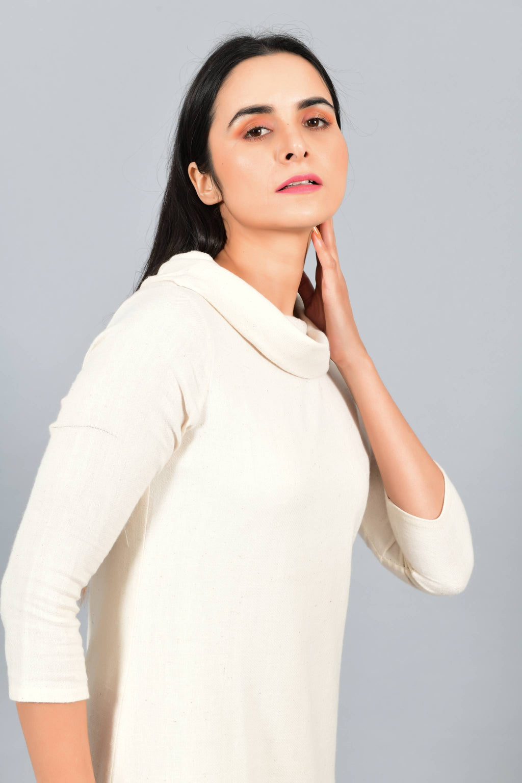 Close Up of an Indian female womenswear fashion model in an off-white Cashmere Cotton Cowl Neck Dress made using handspun and handwoven khadi cotton by Cotton Rack.