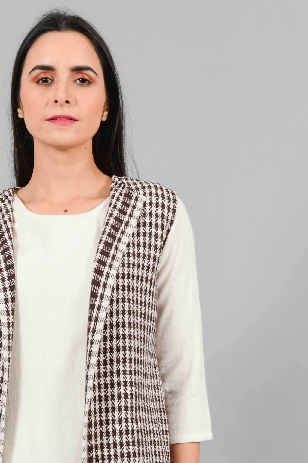 Front close up of an Indian Womenswear female model wearing Kora Brown handspun and handwoven khadi long Jacket over an off-white cashmere cotton dress by Cotton Rack.