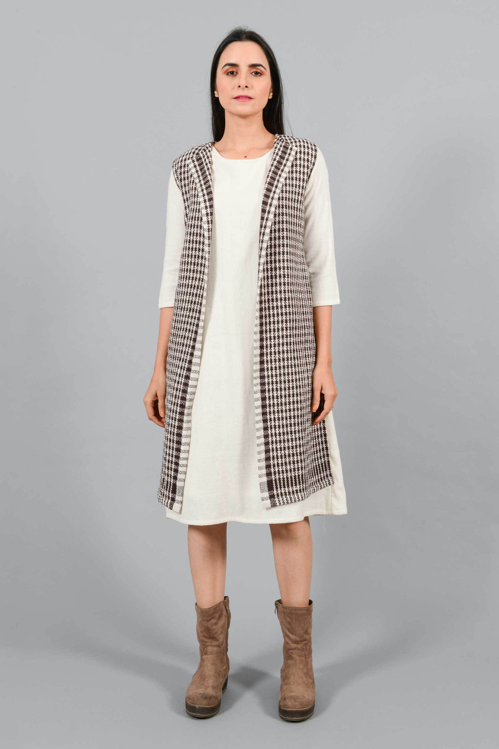 Front pose of an Indian Womenswear female model wearing Kora Brown handspun and handwoven khadi long Jacket over an off-white cashmere cotton dress by Cotton Rack.