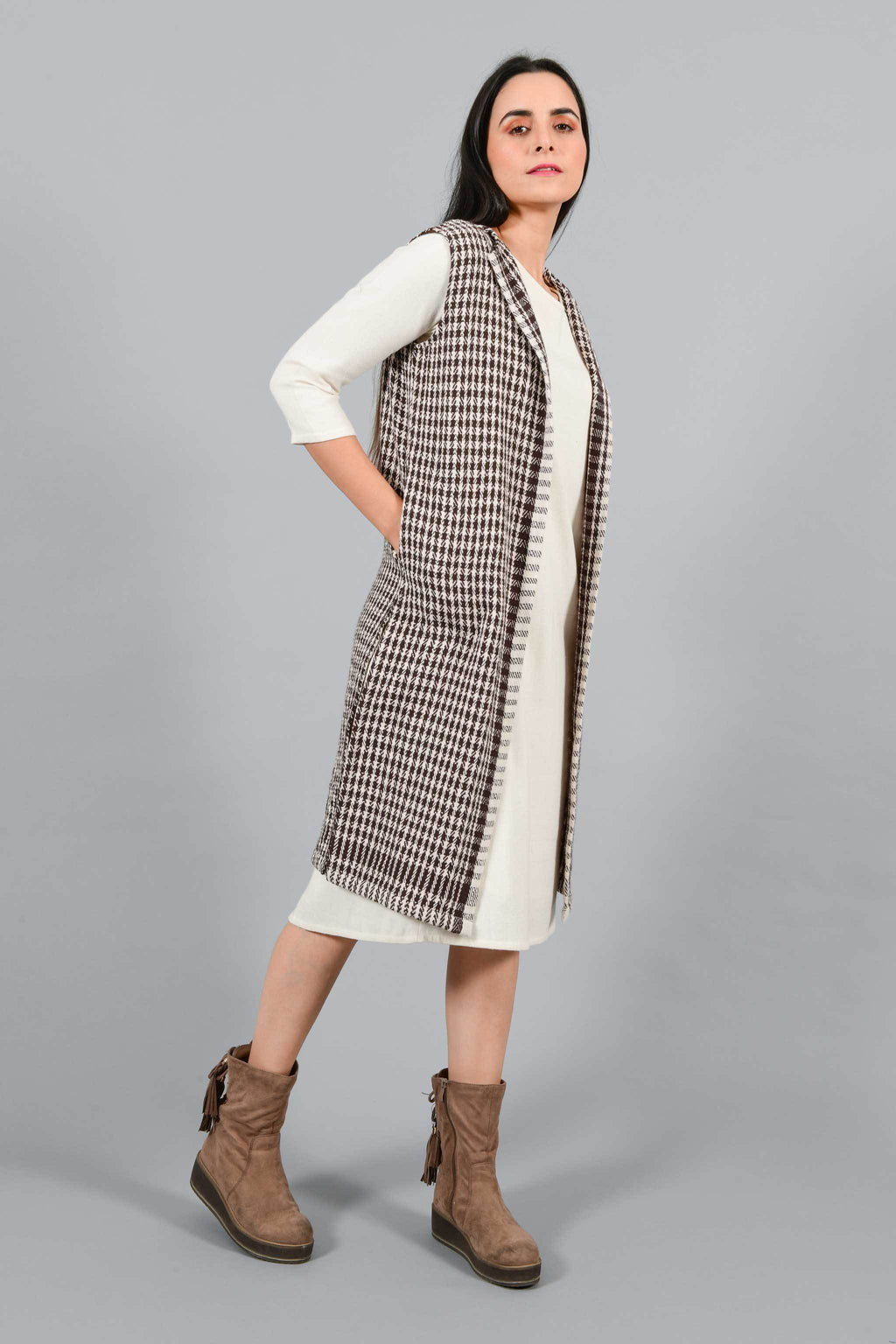 Side pose of an Indian Womenswear female model wearing Kora Brown handspun and handwoven khadi long Jacket over an off-white cashmere cotton dress by Cotton Rack.