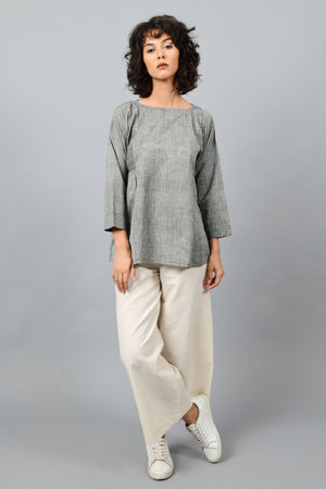 front of a female womenswear fashion model wearing a minimal Black chambray top by Cotton Rack made in handspun handwoven khadi cotton from west bengal