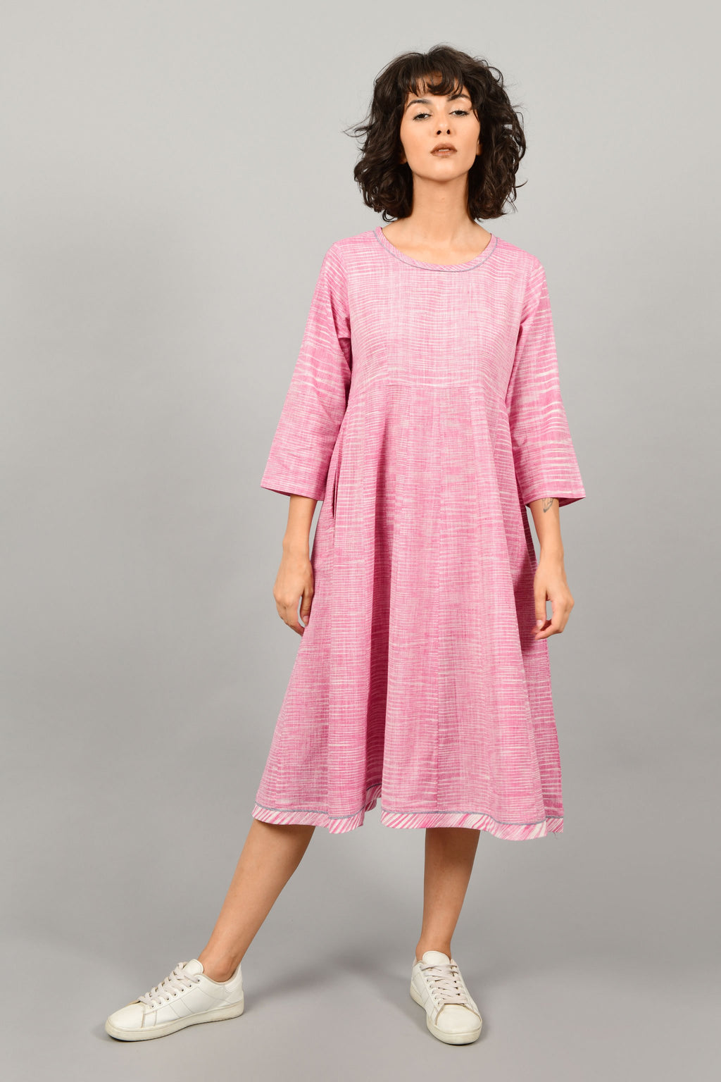 front of a female fashion model wearing a minimal kalidar Indo-western dress kurta by Cotton Rack in purple and white space dyed fine handspun handwoven khadi cotton from west bengal