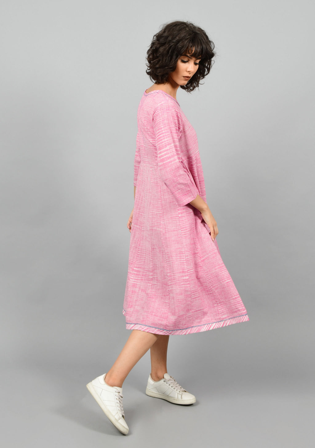 Side pose of a female womenswear fashion model wearing a minimal indo-western kalidar dress kurta by Cotton Rack in purple and white space dyed fine handspun handwoven khadi cotton from west bengal