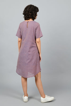 back of a female fashion model wearing a minimally designed western A-line round bottom chequered dress Cotton Rack in fine handspun handwoven khadi cotton from west bengal