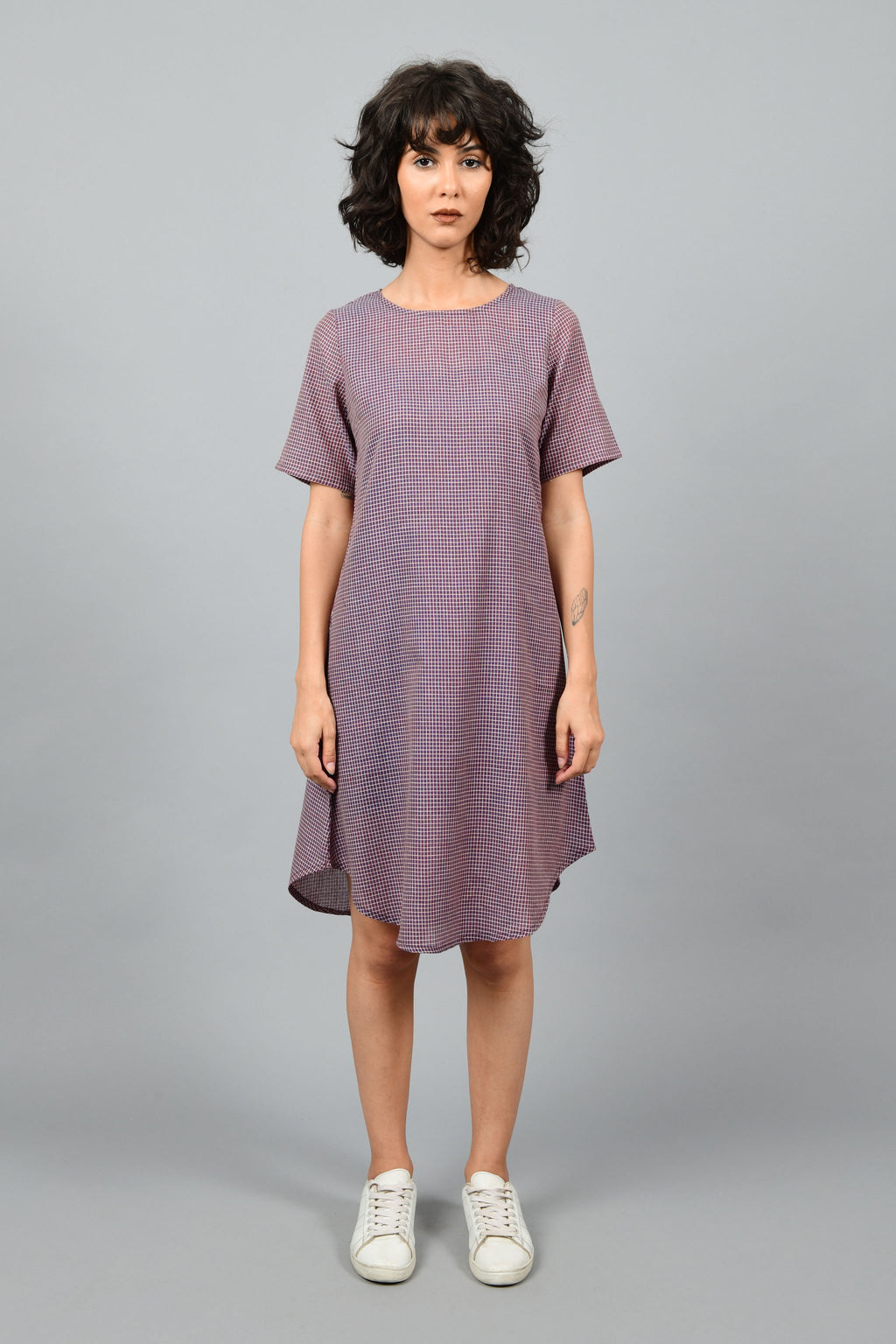 front of a female fashion model wearing a minimally designed western A-line round bottom chequered dress Cotton Rack in fine handspun handwoven khadi cotton from west bengal