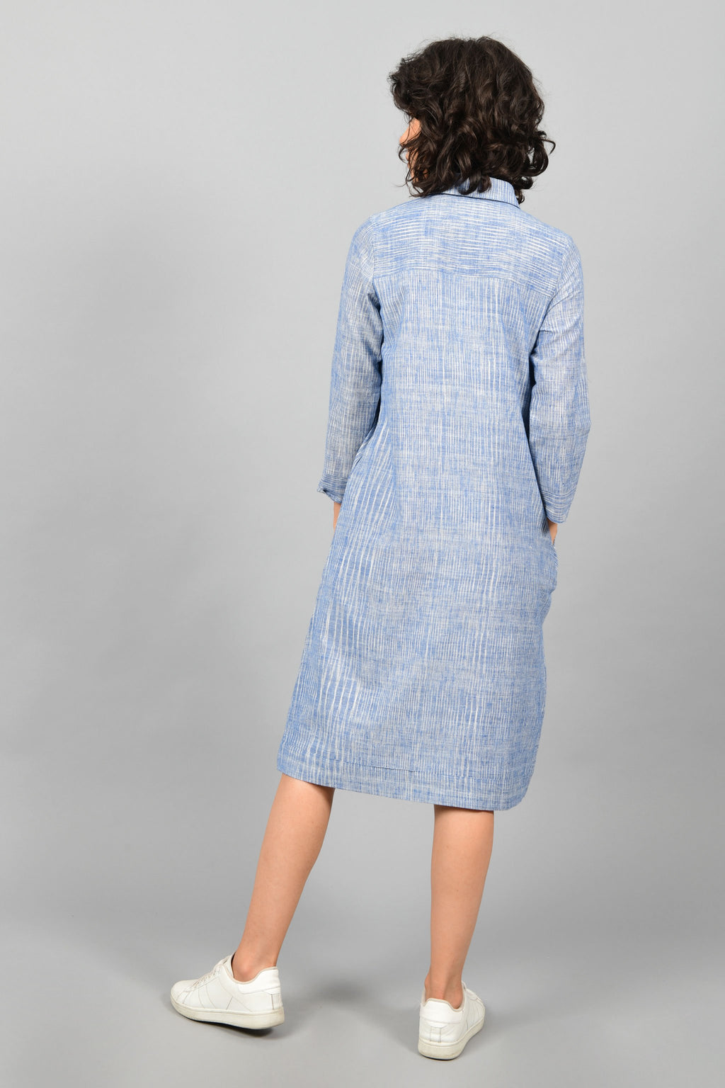 back of a model wearing a shirt dress in blue and white space dyed fine handspun handwoven khadi cotton from west bengal