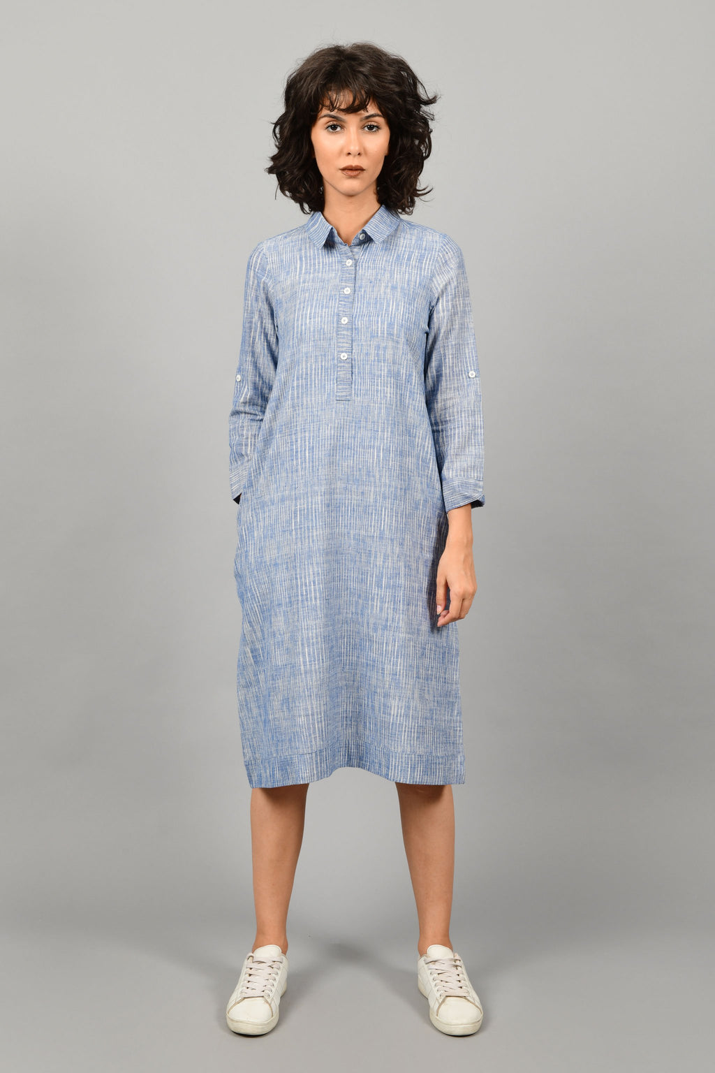 front of a model wearing a shirt dress in blue and white space dyed fine handspun handwoven khadi cotton from west bengal