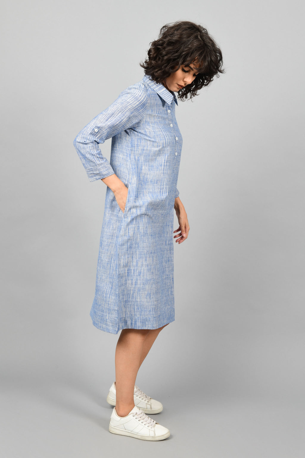 side pose of a model wearing a shirt dress in blue and white space dyed fine handspun handwoven khadi cotton from west bengal