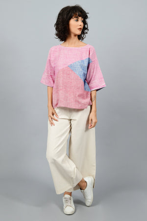 front of a model wearing a crop top blouse with patchwork of pink, blue and red space dyed handspun handwoven khadi cotton from west bengal