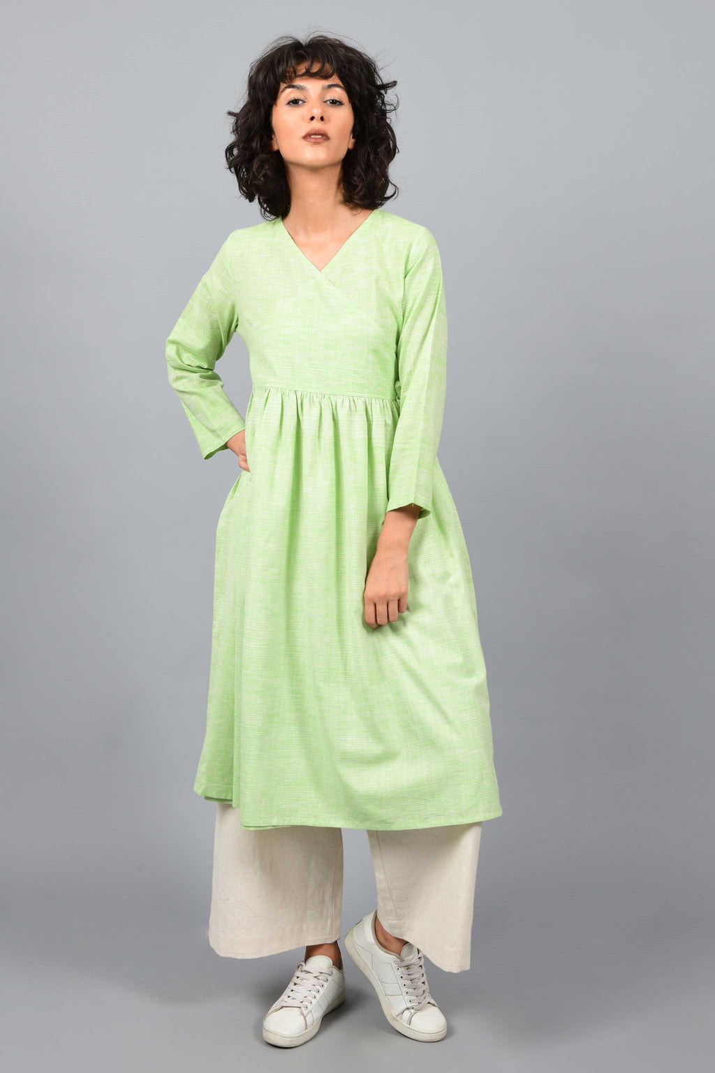 front of a model wearing an angrakha dress kurta in green and white space dyed fine handspun handwoven khadi cotton from west bengal with off white pants