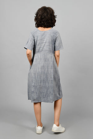 back of a model wearing a front and back pleated dress in fine handspun handwoven khadi cotton from west bengal