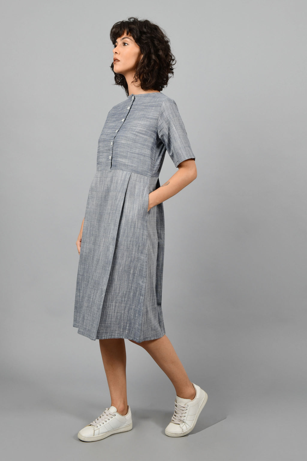 side pose of a model wearing a front and back pleated dress in fine handspun handwoven khadi cotton from west bengal