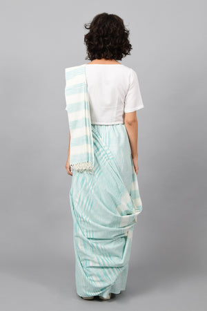 Back pose of a female womenswear fashion model draped in a aquamarine blue & white space dyed homespun and handwoven cotton sari by Cotton Rack.