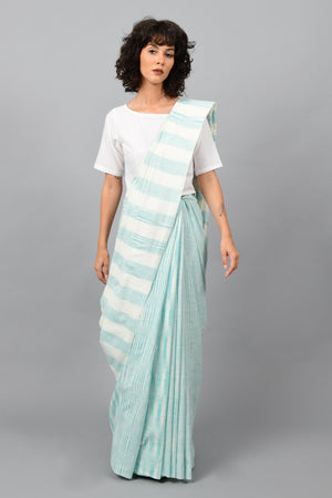 Front pose of a female womenswear fashion model draped in a aquamarine blue & white space dyed homespun and handwoven cotton sari by Cotton Rack.